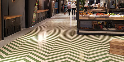 OSB like porcelain tile with green stripes on the OSHI Market floor